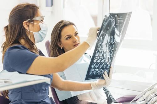 woman and dentist examining x-ray